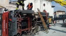 Scarica un bobcat con la gru: camion si ribalta in mezzo alla piazza
