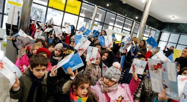 Bambini consegnano le letterine a Babbo Natale negli uffici di Poste Italiane