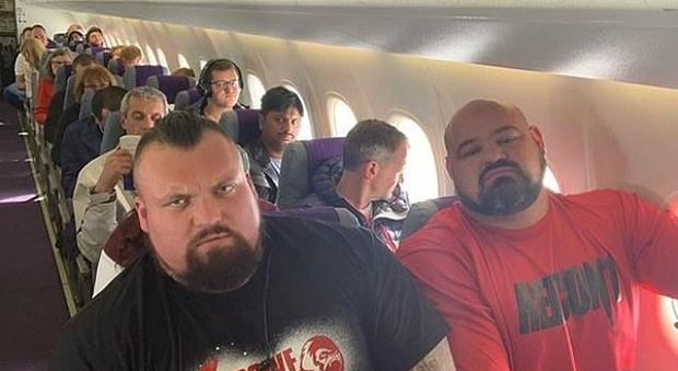 Due campioni di lotta viaggiano in economy uno accanto all'altro, la foto conquista il web