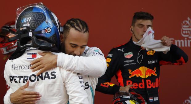 Lewis Hamilton abbraccia il compagno di squadra Bottas, sullo sfondo Verstappen