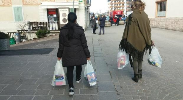 Una turista con la colf che l'aiuta a portare la spesa
