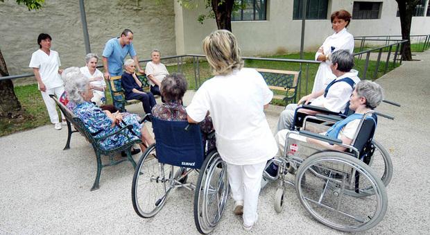 Anziani in una casa di riposo con operatrici e assistenti (Ansa)