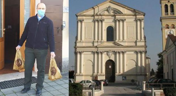 Don Claudio Bosa con le borse della spesa donata, e la chiesa di San Pietro a Camposampiero