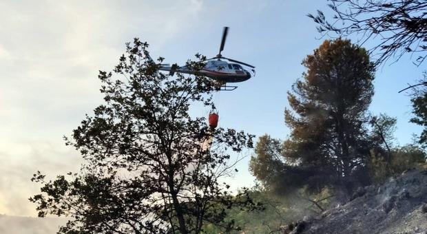 Un elicottero scarica acqua sull'incendio che imperversa nel Piceno. Caccia al piromane