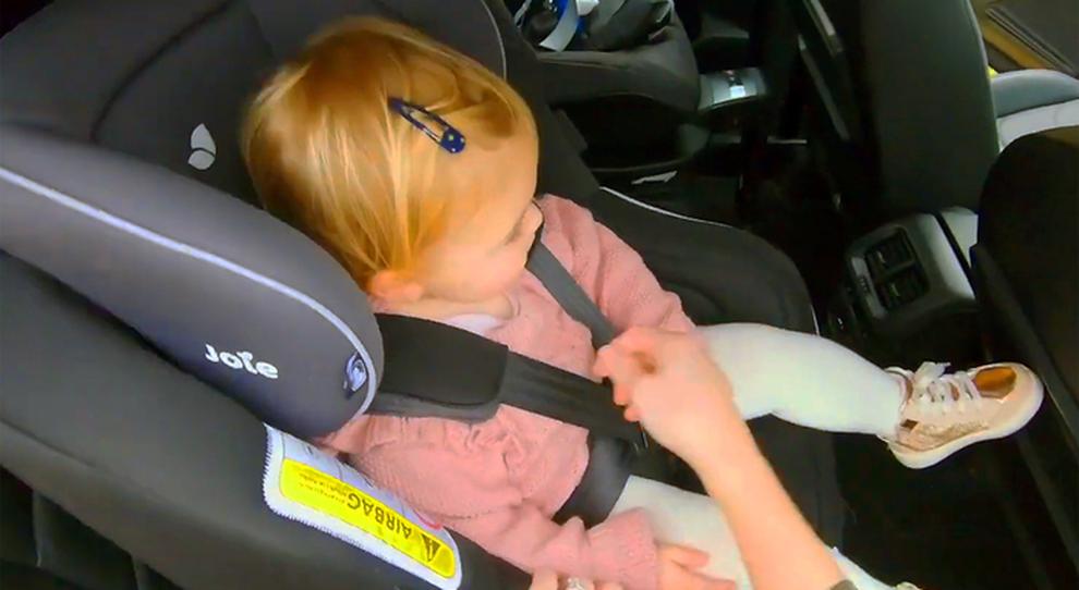 Una bambina in auto dentro al seggiolino