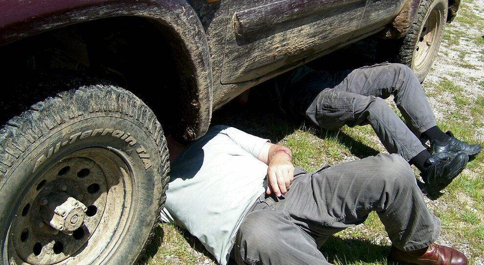 Un uomo al lavoro sotto la sua auto sollevata da un cric