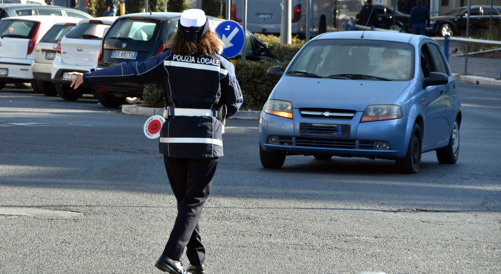 Un agente della Polizia locale ferma un'auto durante il blocco del traffico per un controllo