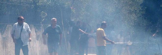 Residenti in strada per spegnere le fiamme