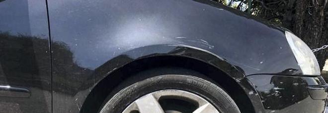 Coppia italiana  dietro alle auto  distrutte e rigate  con le svastiche