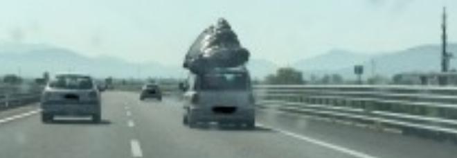 Materasso matrimoniale sul tettuccio dell'auto Famiglia fermata in autostrada