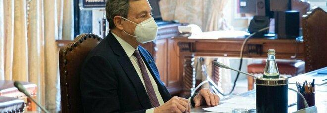 Mario Draghi durante una fase delle consultazioni. Sul tavolo anche un libro con le foto dei parlamentari che incontra